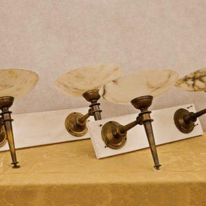 Art.LL.3 - Quattro appliques da parete art decò, in bronzo e alabastro in patina originale, parte elettrica da rifare. Italia 1920/30.