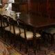Art.TP.1 - Importante tavolo da pranzo/riunione, interamente in legno di noce con piano lastronato noce a riquadri geometrici, sei gambe tornite.